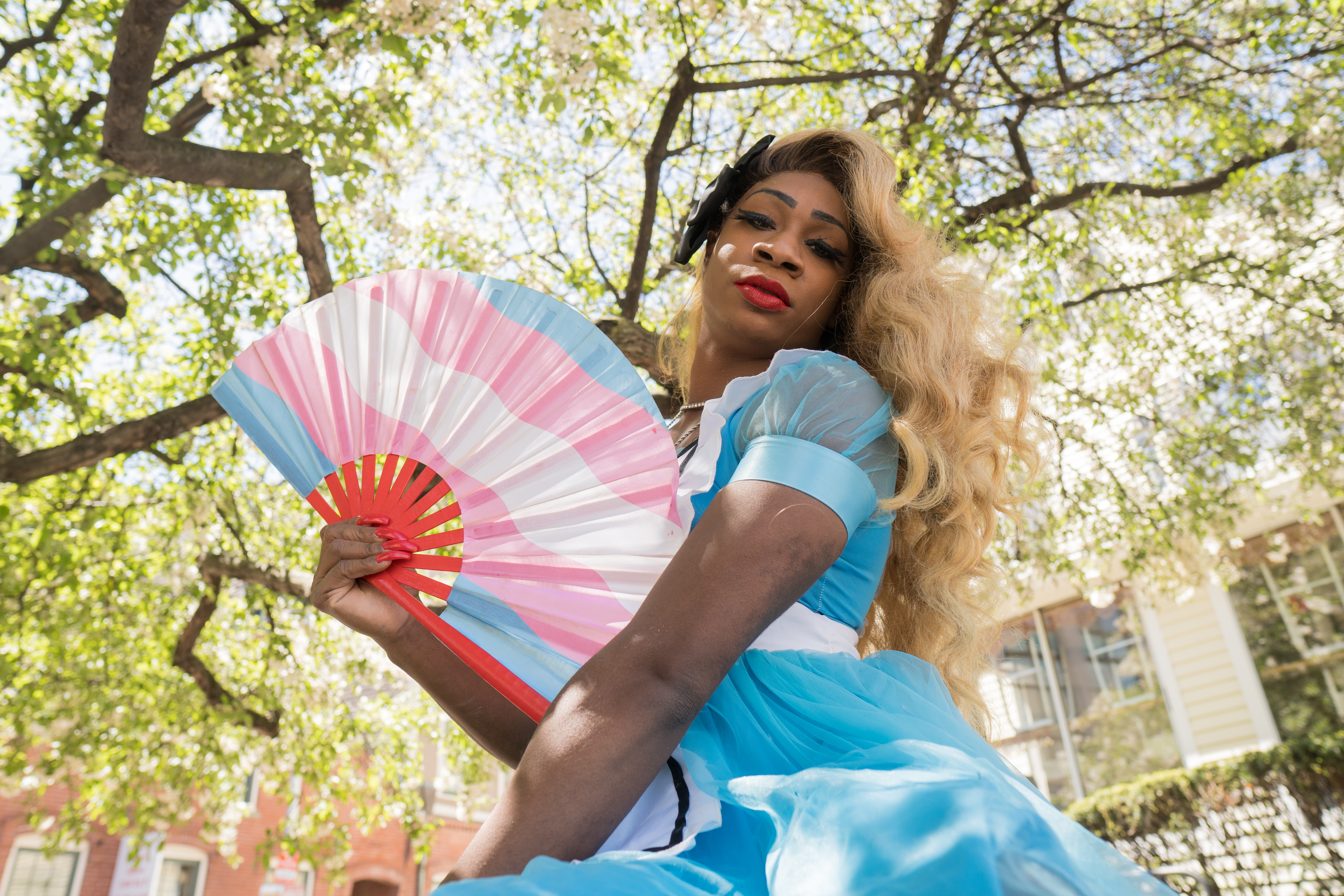 Lilly Rose Valore as Alice with a transgender pride-themed hand fan.